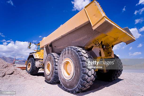 Dump truck showing big tires and blue sky background