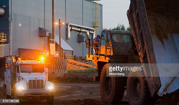 A dump truck unloads soil near the Syncrude Canada Ltd upgrader plant at the company's mine near Fort McMurray Alberta Canada on Tuesday June 2 2015...