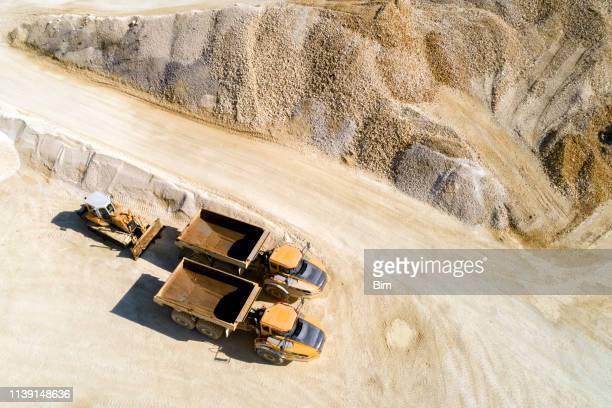 dump trucks and bulldozer in a quarry, aerial view - gravel stock pictures, royalty-free photos & images
