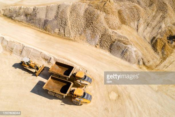 dump trucks and bulldozer in a quarry, aerial view - mining natural resources stock pictures, royalty-free photos & images