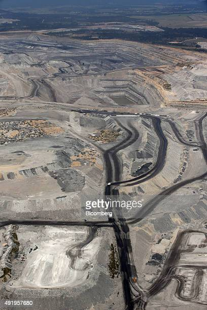 Dump trucks drive along a haul road in an open pit at Glencore Plc's Bulga Coal operations in this aerial photograph taken near Singleton Australia...