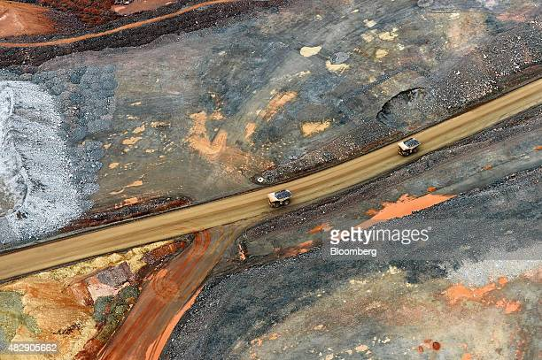 Dump trucks drive along a haul road inside the Fimiston Open Pit mine known as the Super Pit in this aerial photograph taken above Kalgoorlie...