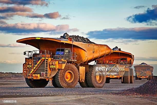 Dump trucks dumping rocks at a gold mine