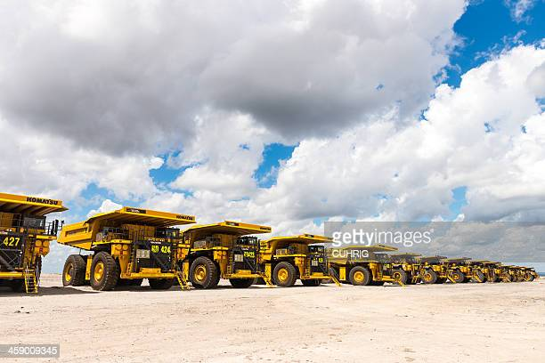 dump trucks parked up due to recession - komatsu stock pictures, royalty-free photos & images