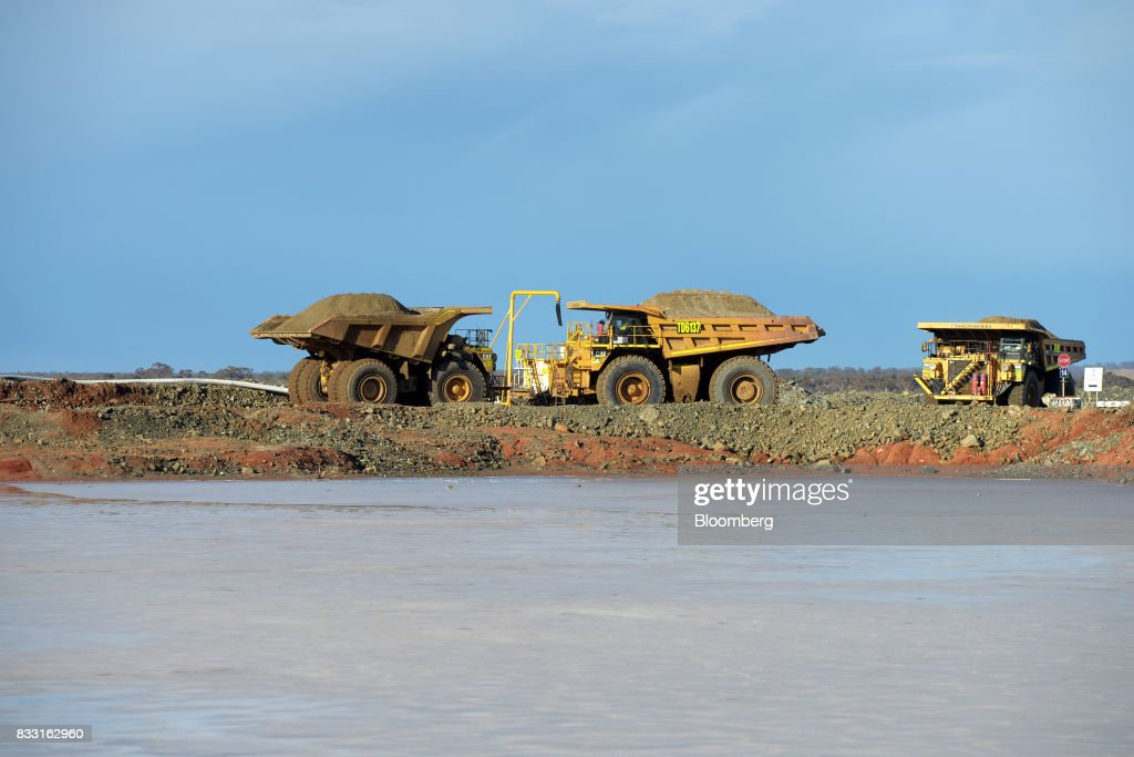 Dump trucks sit beyond a salt lake at the St Ives Gold Mine operated by Gold Fields Ltd. in Kambalda, Australia, on Wednesday, Aug. 9, 2017. Global gold deals have also slowed, declining to $19.8 billion in 2016 from $22.8 billion a year earlier, according to data complied by Bloomberg. Photographer: Carla Gottgens/Bloomberg via Getty Images