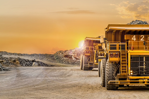 Dump Trucks transporting Platinum ore for processing 1079669214
