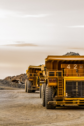 Dump Trucks transporting Platinum ore for processing 1161322483