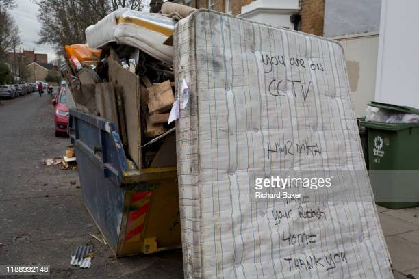 A dumped mattress next to a skip full of licensed waste seen on a nearby shop's CCTV camera which recorded the car's registration number while...