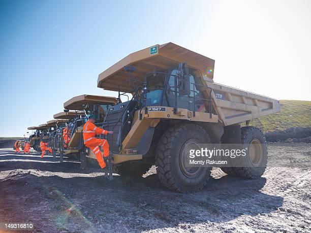 Dumper truck drivers climbing aboard trucks in opencast coalmine