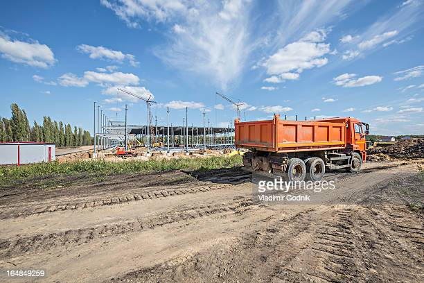Dumper truck parked on dirt track at construction site