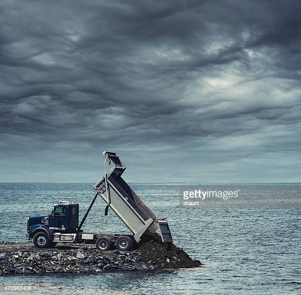 dumping soil into the sea - dump truck stock pictures, royalty-free photos & images