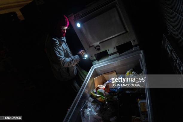 A dumpster diver picks through discarded food items in the back lot of a supermarket in Berlin on May 17 2019 Carrying a penalty that can be up to...