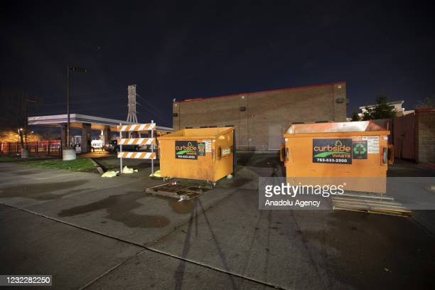 Dumpsters and other items barricade a gas station as its blocked off during curfew as protests over police killing of Daunte Wright continue in...