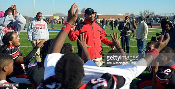 Dunbar's head coach Jerron Joe center has a cheer with his team after the win as Dunbar defeats Anacostia 12 8 in the Turkey Bowl at Eastern High...