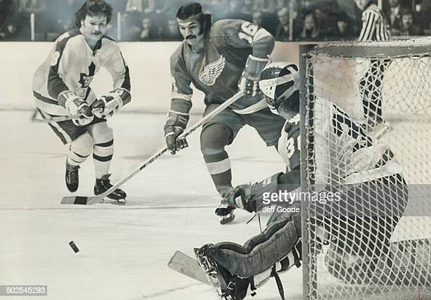 Dunc Wilson Maple Leafs' goalie kicks out puck as teammate Jim McKenny and Detroit Red Wings' Henry Boucha both skate towards rebound in last night's...