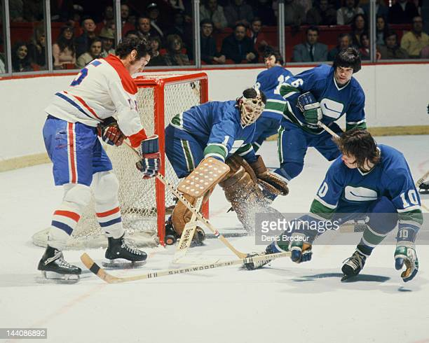 Dunc Wilson of the Vancouver Canucks pokes the puck away from Claude Larose of the Montreal Canadiens Circa 1972 at the Montreal Forum in Montreal...