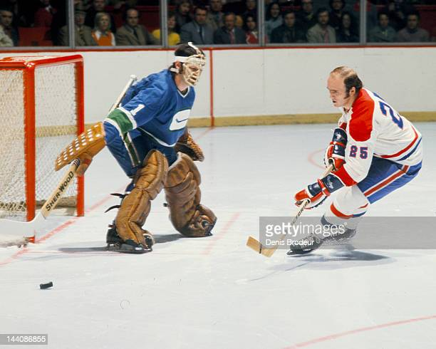 Dunc Wilson of the Vancouver Canucks pokes the puck away from Jacques Lemaire of the Montreal Canadiens Circa 1972 at the Montreal Forum in Montreal...