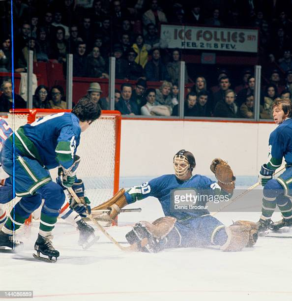 Dunc Wilson of the Vancouver Canucks slides to make a save during game against the Montreal Canadiens Circa 1972 at the Montreal Forum in Montreal...