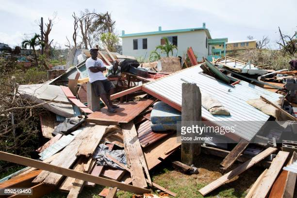 Duncan Edwards and Braumd Phillips stand on a destroyed home on September 23 2017 in Wesley Village Dominica Hurricane Maria inflicted catastrophic...