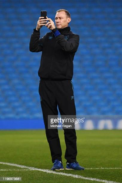 Duncan Ferguson takes a photograph on his phone ahead of the Premier League match between Manchester City and Everton FC at Etihad Stadium on January...