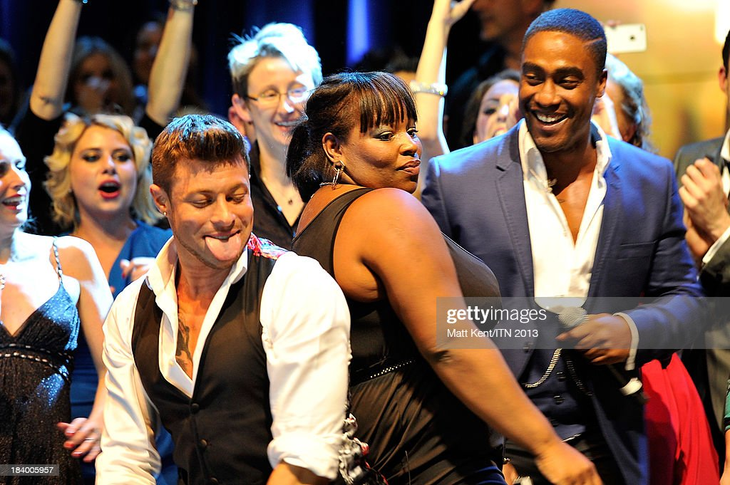 Duncan James (L) and Simon Webbe (R) get close to a member of the Daybreak news team at the annual Newsroom's Got Talent event to raise money for the Leonard Cheshire Disability charity and UNICEF UK at Indigo2 at O2 Arena on October 10, 2013 in London, England.