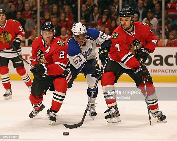 Duncan Keith and Brent Seabrook of the Chicago Blackhawks defend against a charging David Perron of the St Louis Blues at the United Center on...