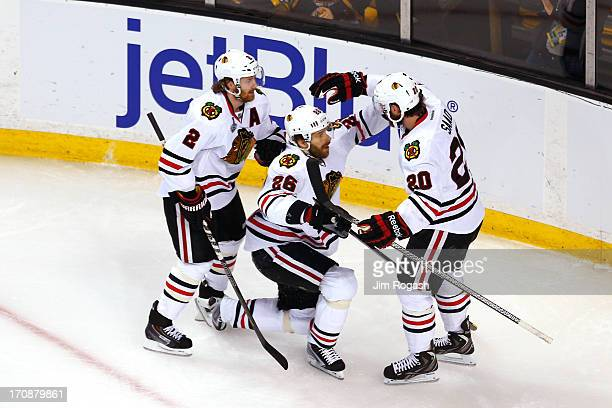 Duncan Keith Michal Handzus and Brandon Saad of the Chicago Blackhawks celebrate after Handzus scores a goal in the first period against the Boston...