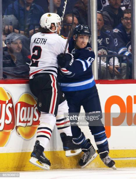 Duncan Keith of the Chicago Blackhawks and Brandon Tanev of the Winnipeg Jets collide along the boards during second period action at the Bell MTS...