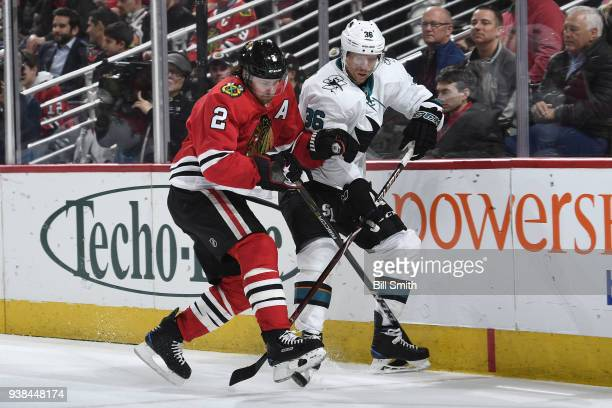 Duncan Keith of the Chicago Blackhawks and Jannik Hansen of the San Jose Sharks chase the puck in the second period at the United Center on March 26...