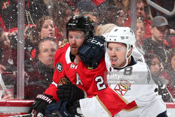 Duncan Keith of the Chicago Blackhawks and Jayce Hawryluk of the Florida Panthers watch for the puck in the third period at the United Center on...