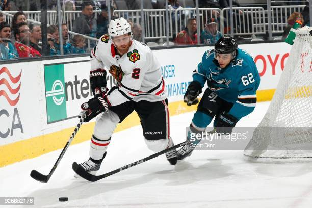 Duncan Keith of the Chicago Blackhawks and Kevin Labanc of the San Jose Sharks battle for the puck at SAP Center on March 1 2018 in San Jose...