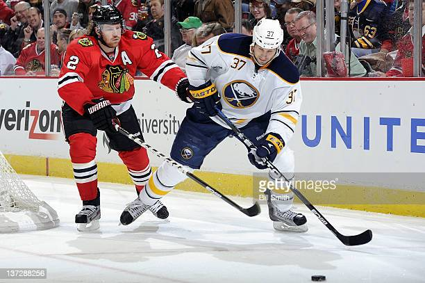 Duncan Keith of the Chicago Blackhawks and Matt Ellis of the Buffalo Sabres chase after the puck during the NHL game on January 18 2012 at the United...