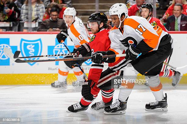Duncan Keith of the Chicago Blackhawks and Wayne Simmonds of the Philadelphia Flyers skate in the first period of the NHL game at the United Center...
