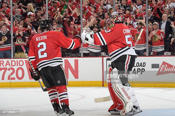 Duncan Keith of the Chicago Blackhawks celebrates with goalie Corey Crawford after Keith scored against the Tampa Bay Lightning in the second period...