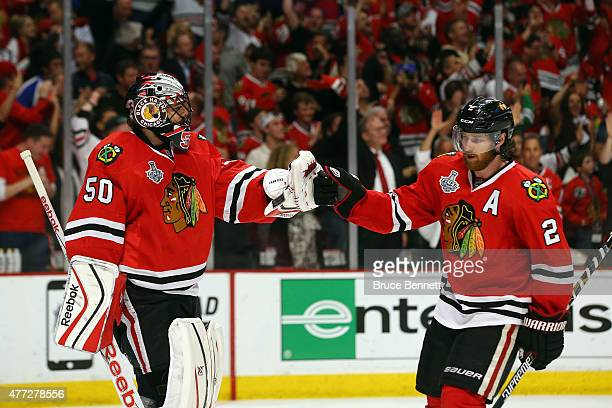 Duncan Keith of the Chicago Blackhawks celebrates with teammate Corey Crawford after scoring a goal in the second period against Ben Bishop of the...