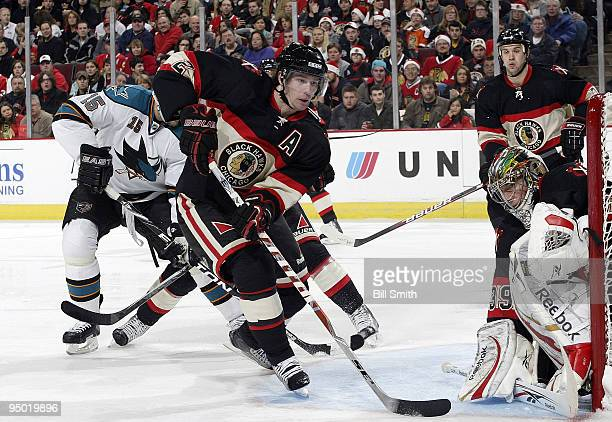 Duncan Keith of the Chicago Blackhawks chases after the puck as teammates Cristobal Huet and Brent Seabrook watch from their position on the ice on...