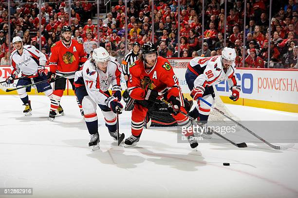 Duncan Keith of the Chicago Blackhawks chases after the puck in between TJ Oshie and Marcus Johansson of the Washington Capitals during the NHL game...