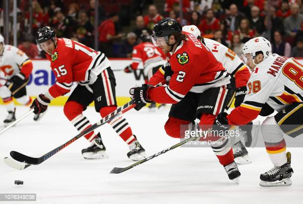 Duncan Keith of the Chicago Blackhawks chases the puck between Matthew Tkachuk and Andrew Mangiapane of the Calgary Flames at the United Center on...
