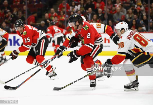Duncan Keith of the Chicago Blackhawks chases the puck between James Neal and Andrew Mangiapane of the Calgary Flames at the United Center on...