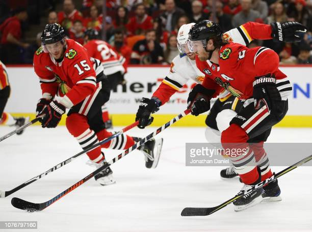 Duncan Keith of the Chicago Blackhawks chases the puck with James Neal of the Calgary Flames at the United Center on December 02 2018 in Chicago...