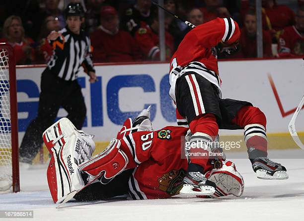 Duncan Keith of the Chicago Blackhawks falls over Corey Crawford in the 2nd period against the Minnesota Wild in Game Two of the Western Conference...