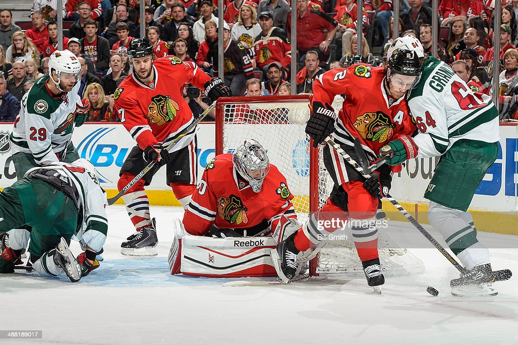 Duncan Keith #2 of the Chicago Blackhawks gets physical with Mikael Granlund #64 of the Minnesota Wild, as Jason Pominville #29 of the Wild, Brent Seabrook #7 and goalie Corey Crawford #50 of the Blackhawks watch the puck from behind, in Game Two of the Second Round of the 2014 Stanley Cup Playoffs at the United Center on May 04, 2014 in Chicago, Illinois.