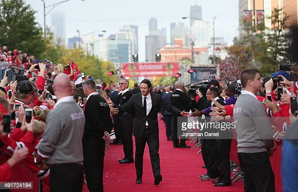 Duncan Keith of the Chicago Blackhawks greets fans as he walks down the red carpet before the first home game against the New York Rangers during an...