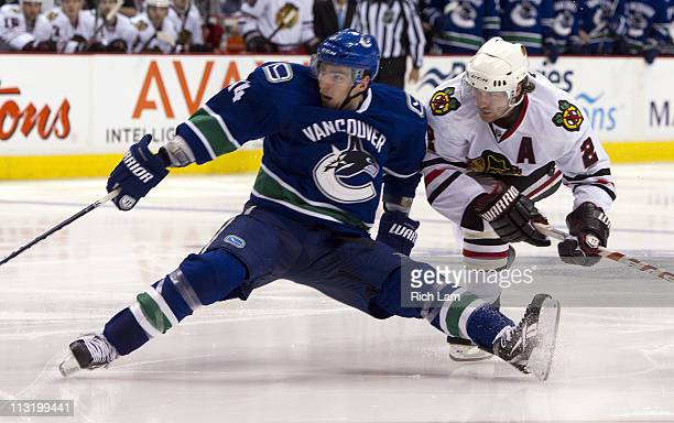 Duncan Keith of the Chicago Blackhawks hauls down Alexandre Burrows of the Vancouver Canucks during the third period in Game Seven of the Western...
