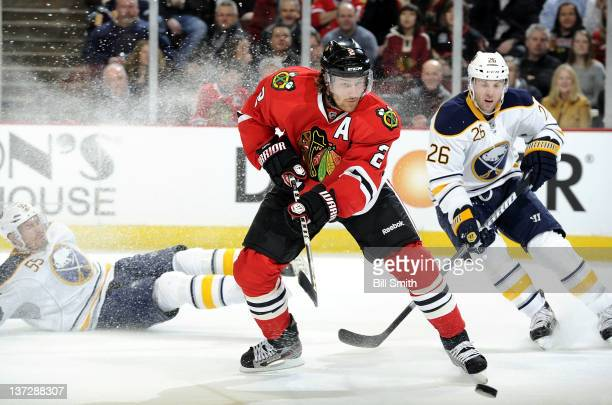 Duncan Keith of the Chicago Blackhawks hits the puck as Thomas Vanek of the Buffalo Sabres chases behind and Jochen Hecht of the Sabres falls on the...