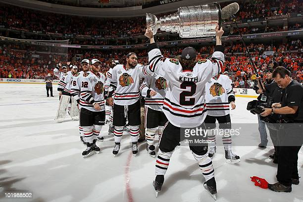 Duncan Keith of the Chicago Blackhawks hoists the Stanley Cup after teammate Patrick Kane scored the game-winning goal in overtime to defeat the...