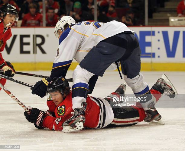 Duncan Keith of the Chicago Blackhawks is knocked to the ice by Patrik Berglund of the St Louis Blues at the United Center on February 19 2012 in...