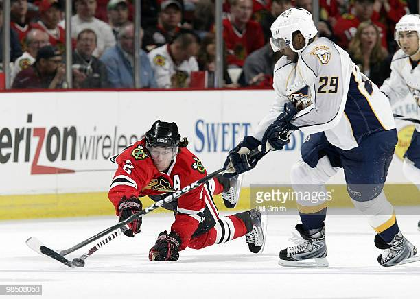 Duncan Keith of the Chicago Blackhawks leaps toward the puck as Joel Ward of the Nashville Predators reaches across at Game One of the Western...