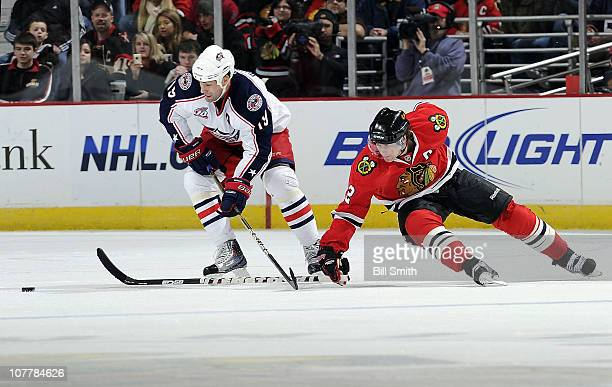 Duncan Keith of the Chicago Blackhawks reaches from behind Ethan Moreau of the Columbus Blue Jackets toward the puck on December 26 2010 at the...