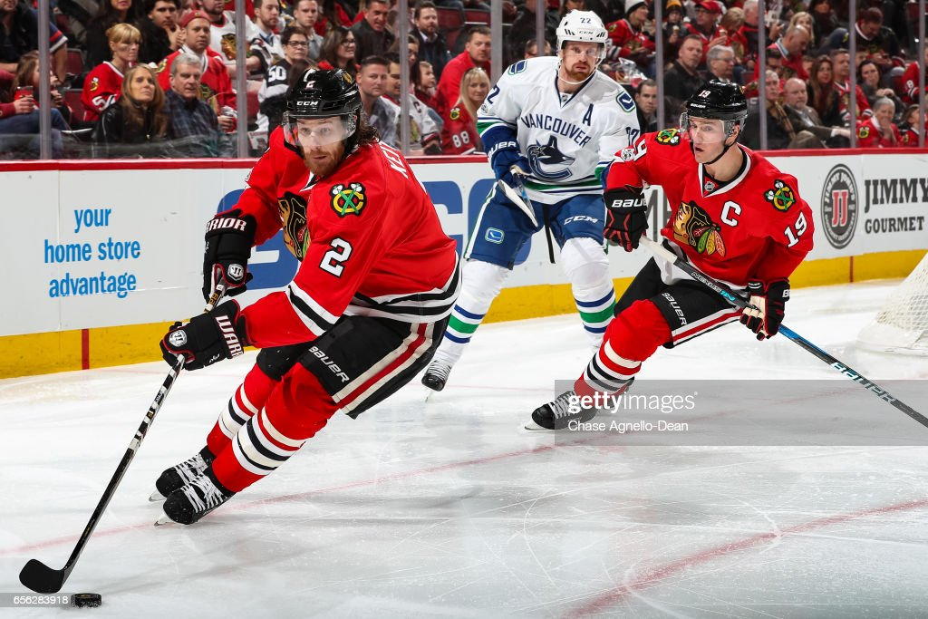 Duncan Keith #2 of the Chicago Blackhawks takes control of the puck ahead of Jonathan Toews #19 and Daniel Sedin #22 of the Vancouver Canucks in the third period at the United Center on March 21, 2017 in Chicago, Illinois.